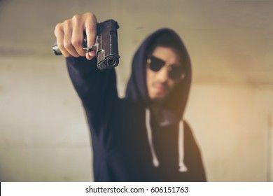 hooded-criminal-gesturing-gun-shootingspooky-260nw-606151763.jpg
