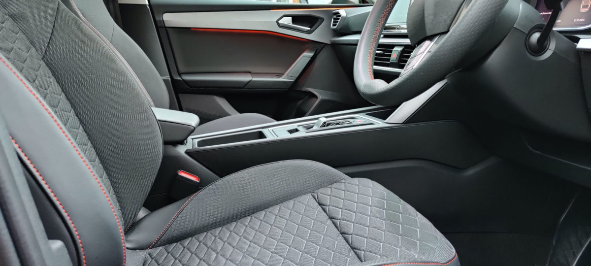 Seats with side bolsters and cross hatch material pattern with red stitching